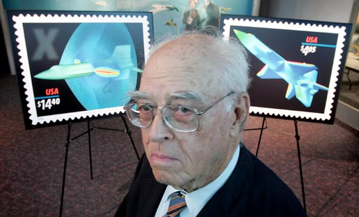 Former X-15 engineer Jim Penland stands in front of displays of the new stamps