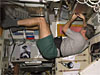 An astronaut dressed in shorts and a t-shirt floats in microgravity while he works on equipment on the ISS