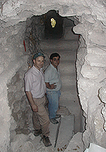 Two men standing in a cave-like opening