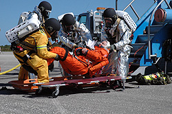A simulation volunteer is lowered onto a litter by rescue crews.