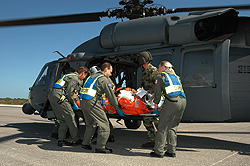 A volunteer is carried to a waiting U.S. Air Force helicopter.