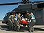 A simulation volunteer is carried to a waiting helicopter.