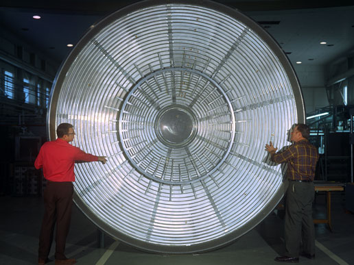 Scientists stand in front of the aeroshell that protected the Viking Lander I during its entry into the Martian atmosphere.