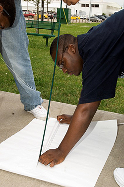 A student measures a shadow created by the sun