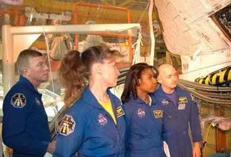 STS-121 crew members examine an orbiter at Kennedy Space Center.