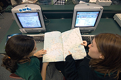 Two students use a map and the Internet to find coordinates for their next picture