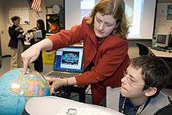 NASA scientist uses a globe to show a student a potential photo target