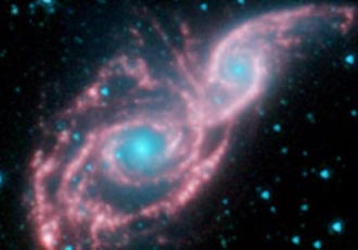 false-colored image of two merging galaxies, NGC 2207 and IC 2163