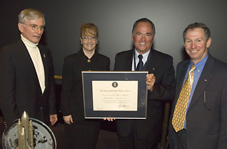 Crippen holds award citation with, from left, STS-1 Commander John Young, NASA Deputy Administrator Shana Dale, and NASA Administrator Michael Griffin