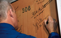 JSC2006-E-11916 - Jeff Williams signs bedroom door at the Cosmonaut Hotel.