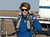 Female pilot in a blue flight suit and dark sunglasses