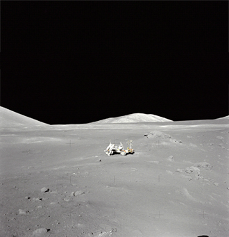 An extraordinary lunar panorama at Station 4 (Shorty Crater) showing Geologist-Astronaut Harrison H. Schmitt working at the Lunar Roving Vehicle (LRV) during the second Apollo 17 extravehicular activity (EVA-2) at the Taurus-Littrow landing site. This is the area where Schmitt first spotted a mysterious orange soil.  Shorty Crater is to the right. The peak in the center background is Family Mountain. A portion of South Massif is on the horizon at the left edge.  Apollo 17 was the last voyage of Apollo.