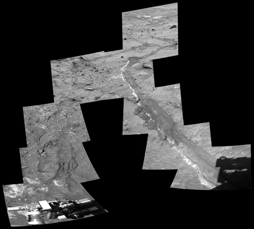 Image shows a pair of rover tracks moving toward the viewer across a sandy.