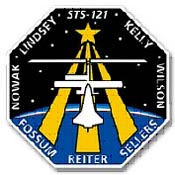 The STS-121 patch features the names of the crew and a drawing of the shuttle docked with the space station in front of a star with three long rays and a background showing the Earth and a star field