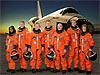 The STS-121 crew in orange shuttle launch and entry suits standing in front of the space shuttle