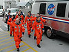 STS-121 crew members walk to the transport van.