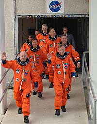 The STS-121 crew members leave the Operations and Checkout building
