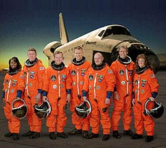 Seven astronauts in their orange shuttle launch and entry suits pose in front of the Discovery orbiter