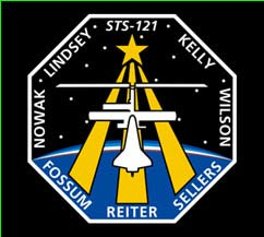 The names of the STS-121 crewmembers surround the edge of a black octagonal-shaped patch. White outline drawings of the space shuttle and space station are on top of gold lines connecting to a gold star in the middle of the patch.