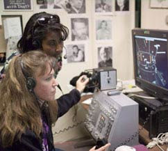 Two female astronauts work at a computer station