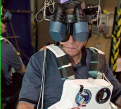 An astronaut's face is almost completely covered by the goggles of the virtual reality mask he is wearing