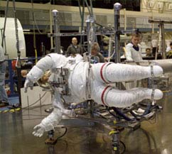 An astronaut in a bulky white space suit hangs sideways in the air from a piece of equipment that is helping him practice for a real spacewalk