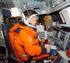 An astronaut sits in a space vehicle simulator wearing an orange shuttle launch and entry suit and a large helmet
