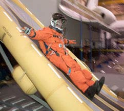 An astronaut in an orange shuttle launch and entry suit and white helmet slides down an inflatable yellow escape slide
