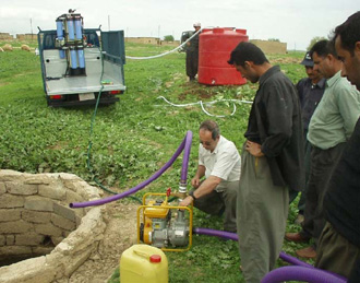 Volunteers in northern Iraq help install and test a water purification system.