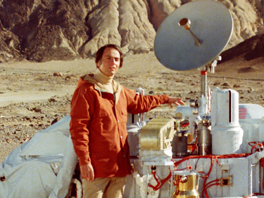 Carl Sagan poses with a model of the Viking lander.