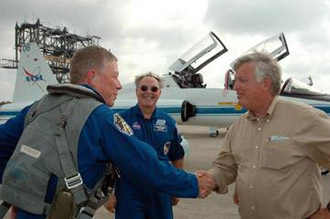 STS-121 Mission Specialist Michael Fossum (left) is greeted by Center Director Jim Kennedy