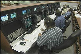 Launch managers working at their computer consoles.