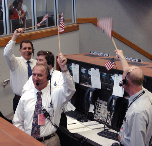 In Firing Room 4 of the Launch Control Center, employees wave American flags after the successful launch of Space Shuttle Discovery.
