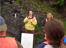 A teacher signs to students as she stands in front of a rock formation