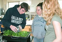 Two students look on as a student waters plants growing in a plant growth chamber