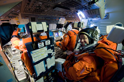 STS-133 astronauts rehearse launch in simulator.