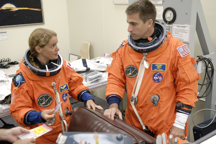 STS-127 Mission Specialists Julie Payette and Christopher Cassidy check equipment