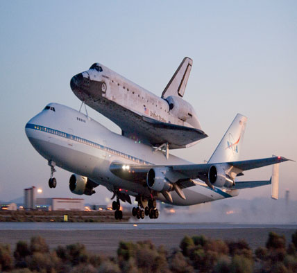 Space shuttle Discovery and its modified 747 carrier aircraft lift off from Edwards.