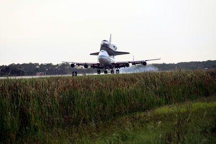 The Shuttle Carrier Aircraft with space shuttle Atlantis secured to its back land in Florida.