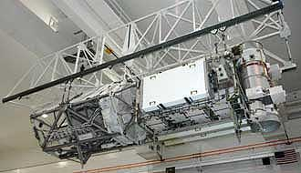 The integrated P3/P4 truss segment hangs suspended in the Space Station Processing Facility.