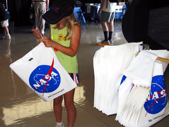 A young lady fills her NASA bag with mementos from Oshkosh 2006