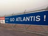 A banner reading Go Atlantis spans a fence along the shuttle's path.