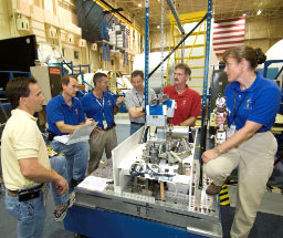JSC2006-E-28149 -- STS-115 astronauts view space gear