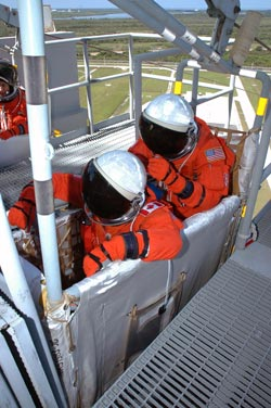 Mission Specialists MacLean and Tanner in a slidewire basket.