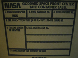 Pictured is the side of a blank Tape Container box. Boxes like these likely contain the tapes in question and have tracking information filled out on the label from when they were initially sent to the National Records Center. Each box can contain up to five data tapes.