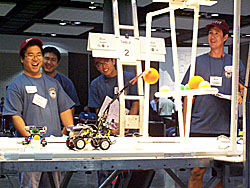 Four volunteers watch a robot on a tournament table