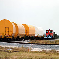 Train pulling three railcars containing parts for the Space Shuttle