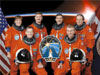 The STS-115 crew posing in their orange launch and entry suits