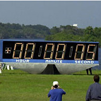 People standing near a large countdown clock showing five seconds remaining