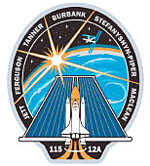 The STS-115 mission patch shows images of the shuttle and a solar array in front of a sunrise over the Earth's horizon, with the space station in the background. The names of the crewmembers circle the edge of the patch.